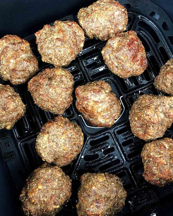 cooked meatballs in an air fryer basket