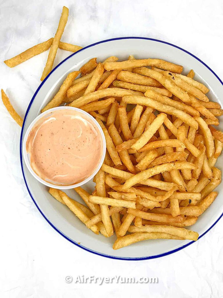 A grey plate with a blue rim that has French fries and a bowl of an orangish dipping sauce