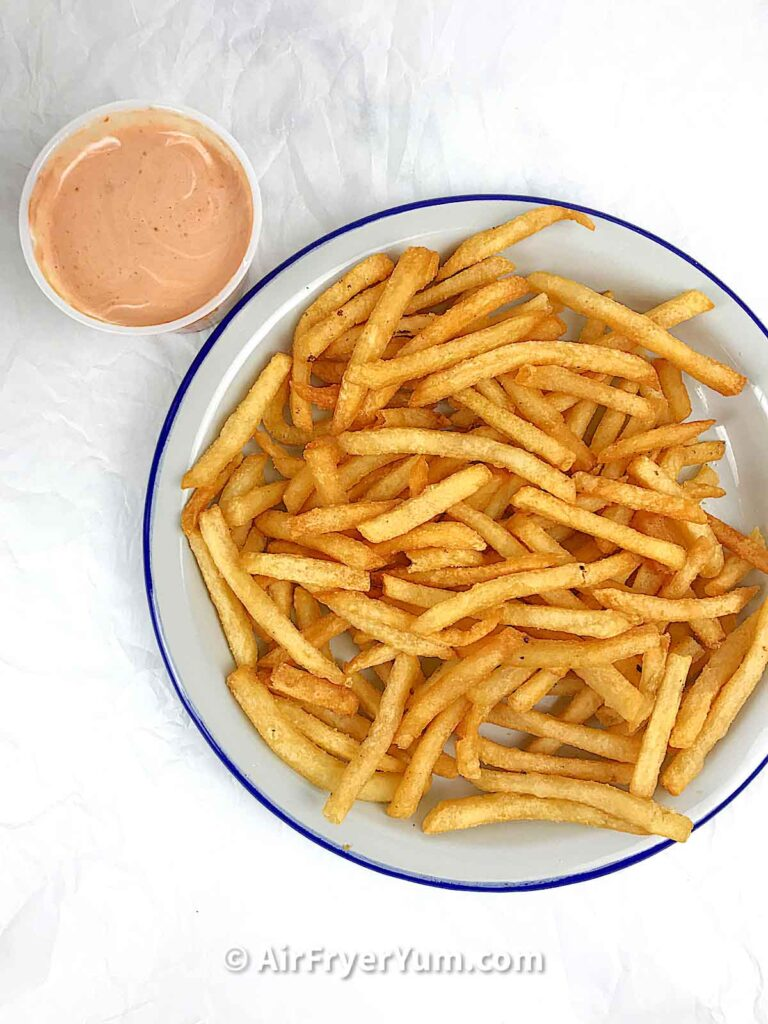 A grey plate of fries with a bowl dipping sauce on the top left corner