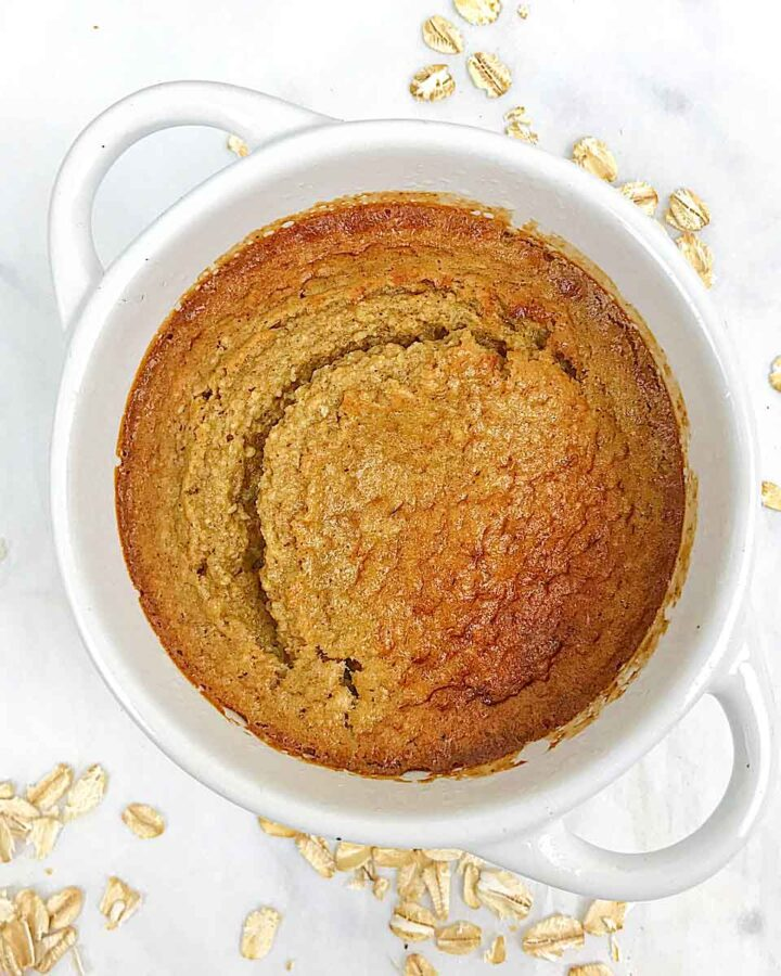 baked oats in a white ramekin with oat pieces all around the white table